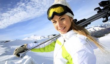 Frau mit Ski auf den Schultern