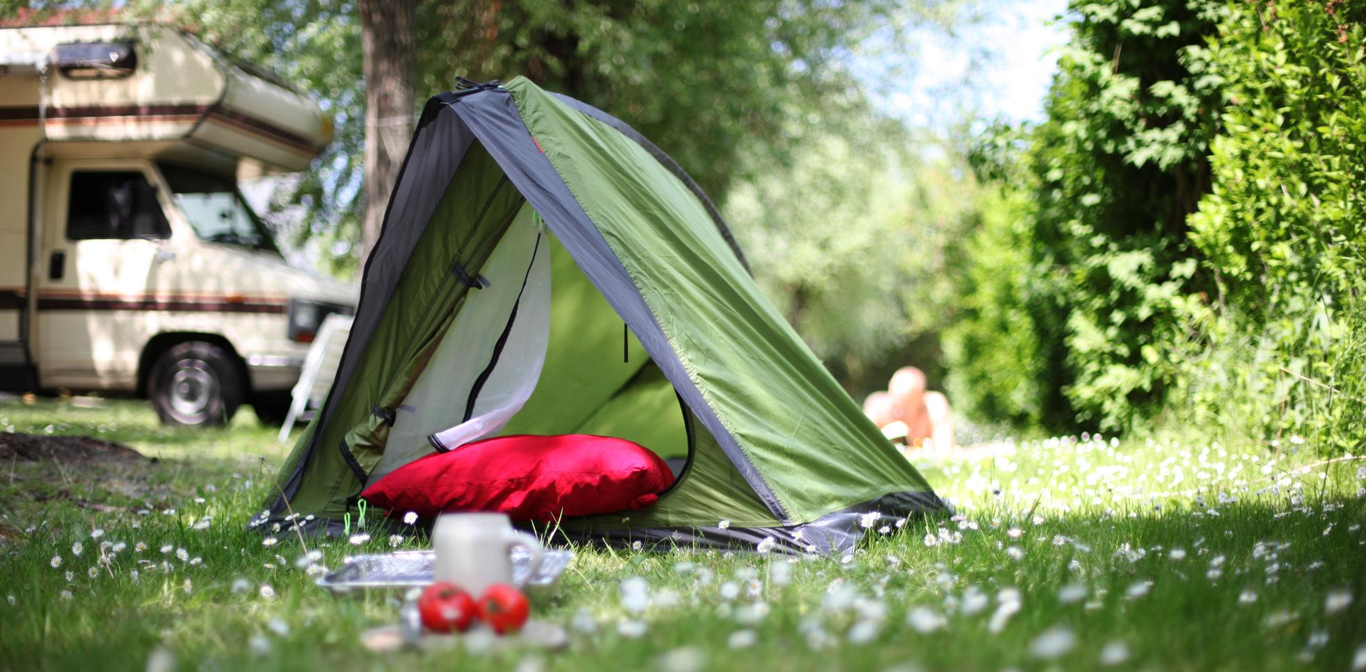Zelt auf einer gruenen Wiese, im Hintergrund ein Wohnmobil