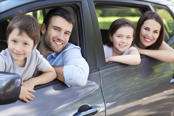 Eine Familie im Mietwagen unterwegs in den Urlaub